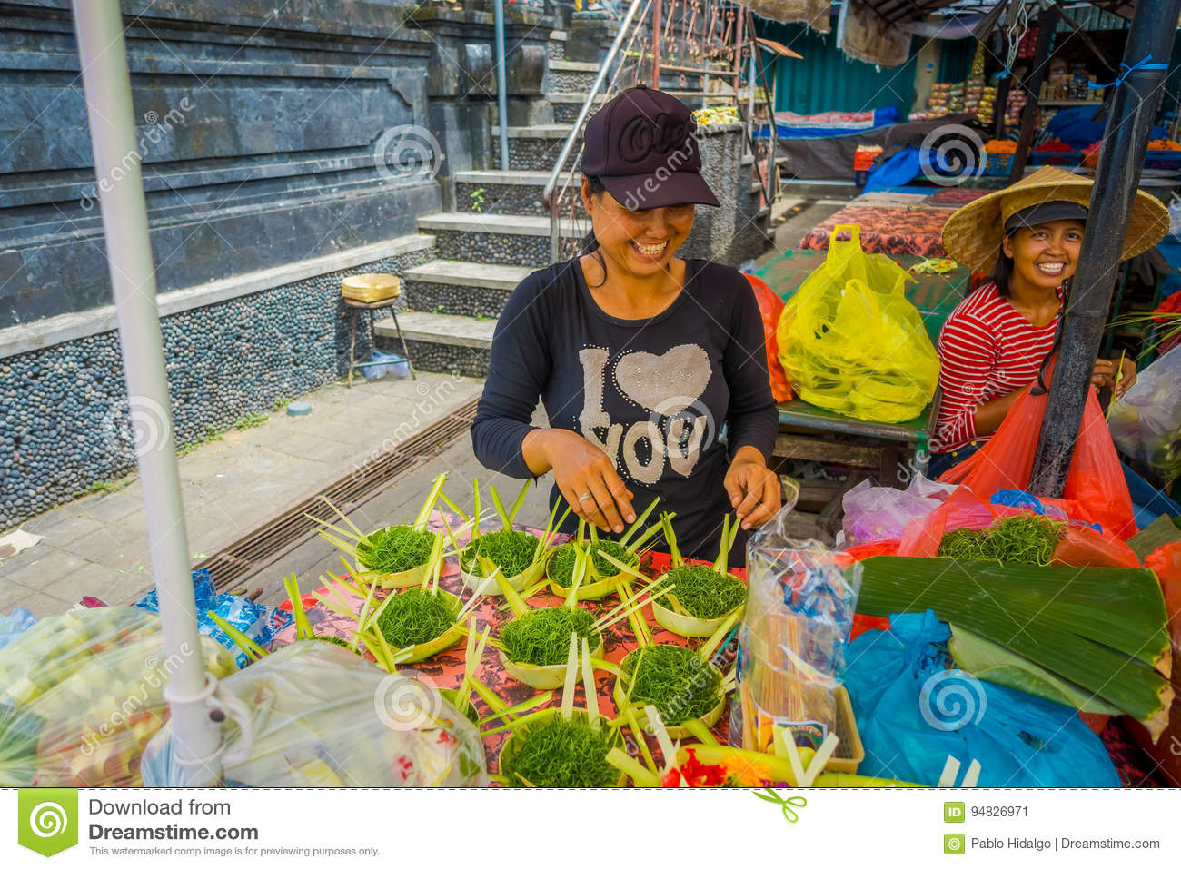 BALI, INDONESIA - MARCH 08, 2017: Unidentified woman do an arrangement of flowers inside of a box made of leafs in a