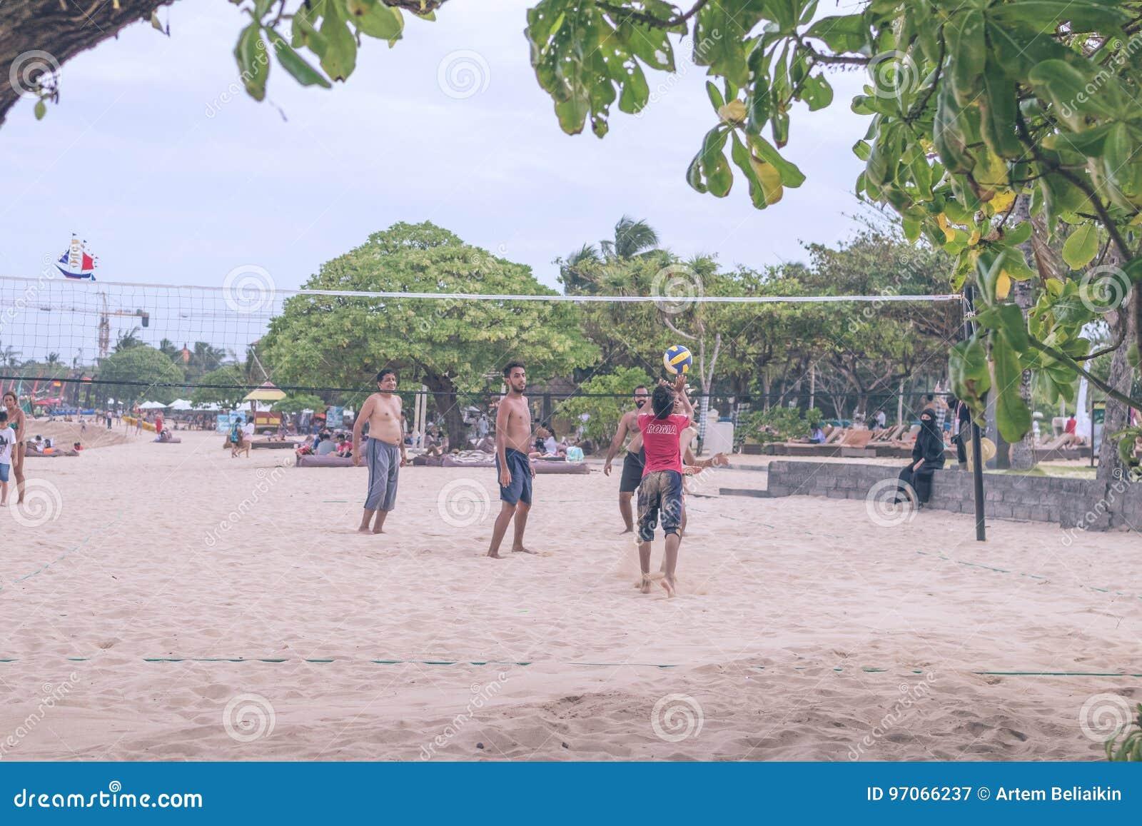 BALI INDONESIEN - JULI 27, 2017: Grupp av vänner som spelar strandsalvan - Mång--etik grupp människor som har gyckel på