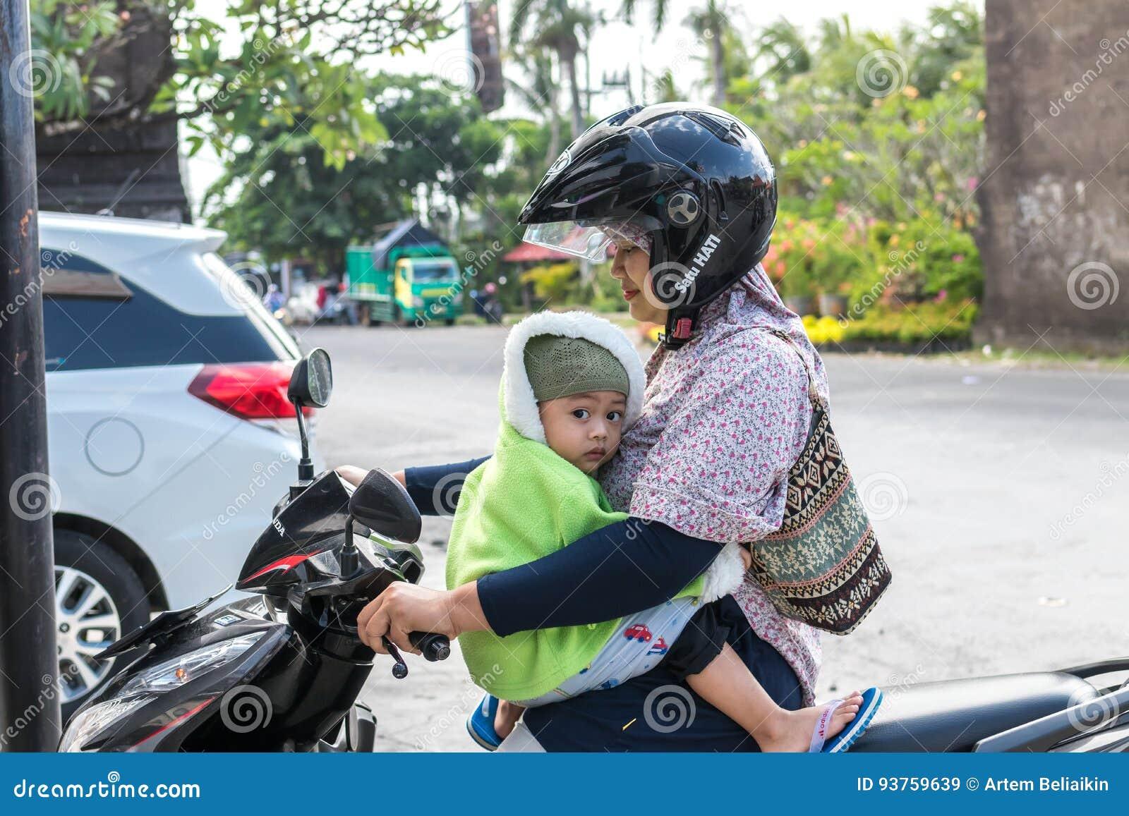 BALI INDONESIEN - JUNI 2, 2017: Stående av balinesemodern med hennes barn i händer som sitter på mopeden