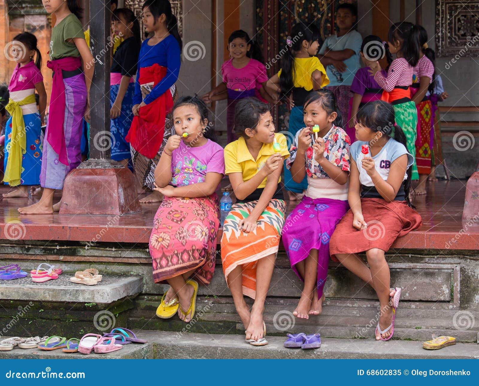 Balijczyk dziewczyna odpoczywa po tym jak szkoła i łasowanie lody tanczymy Ubud, Indonezja