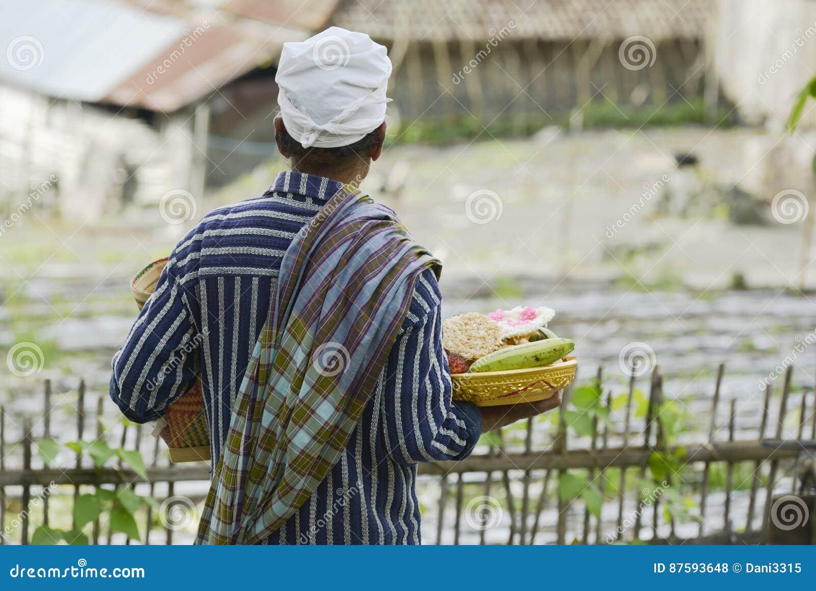 Balijczyka mężczyzna przynosi tradycyjną ofiarę Hinduska świątynia