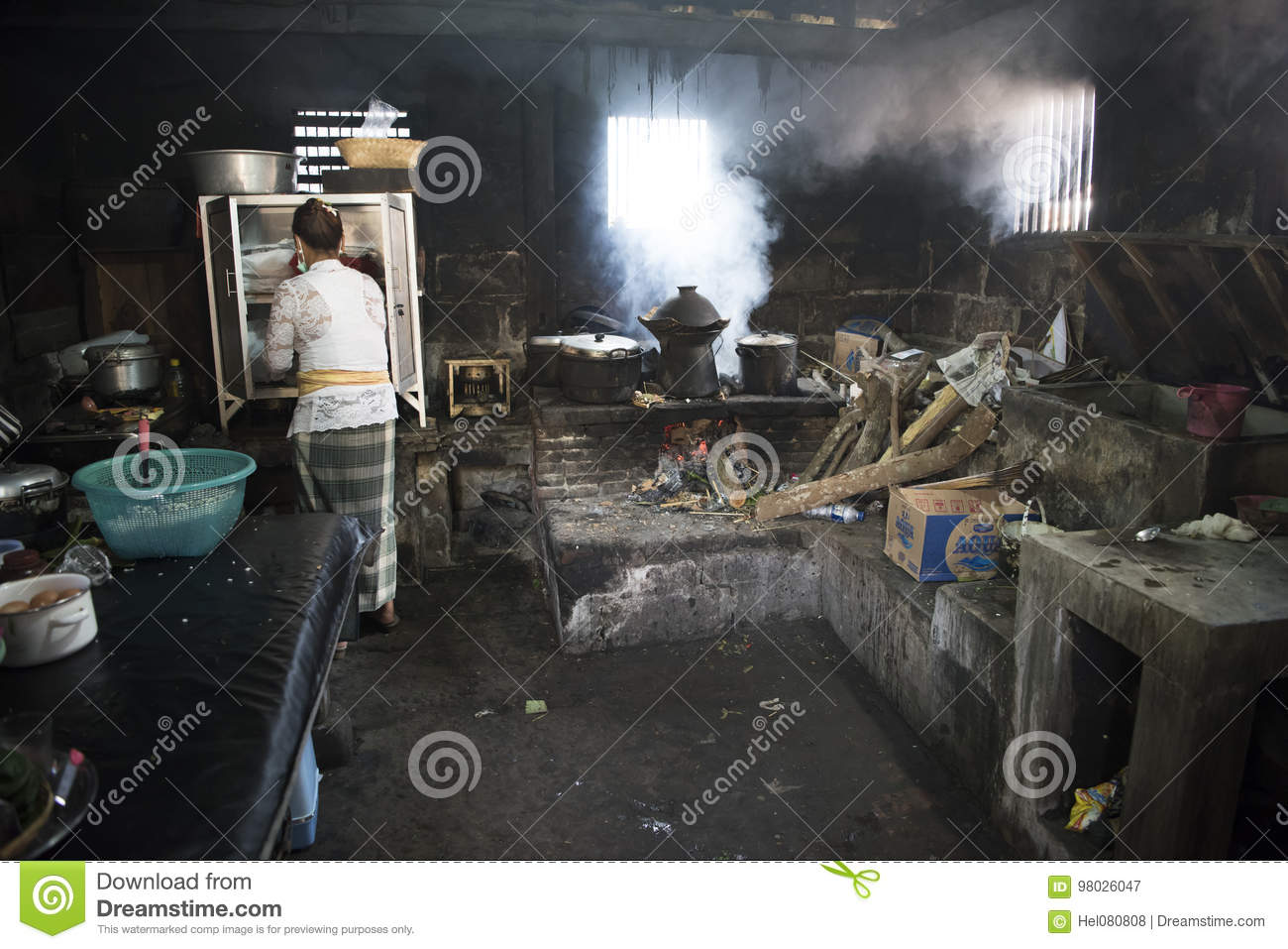 Balinese woman cooking in traditional kitchen