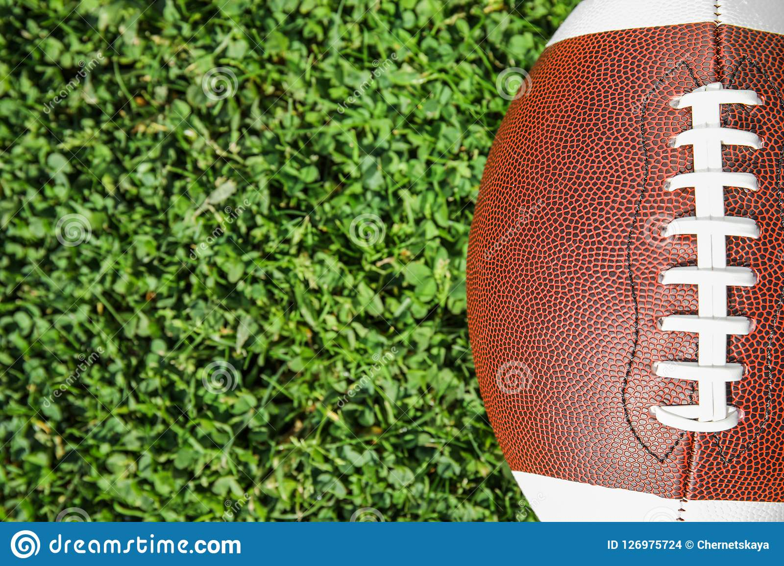 Ball for American football on fresh green field grass, top view