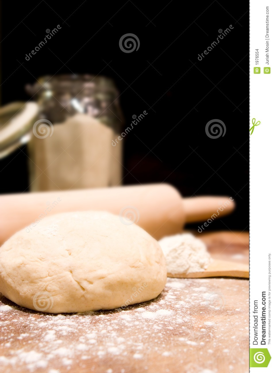Ball of kneaded dough, rolling pin with scattered flour