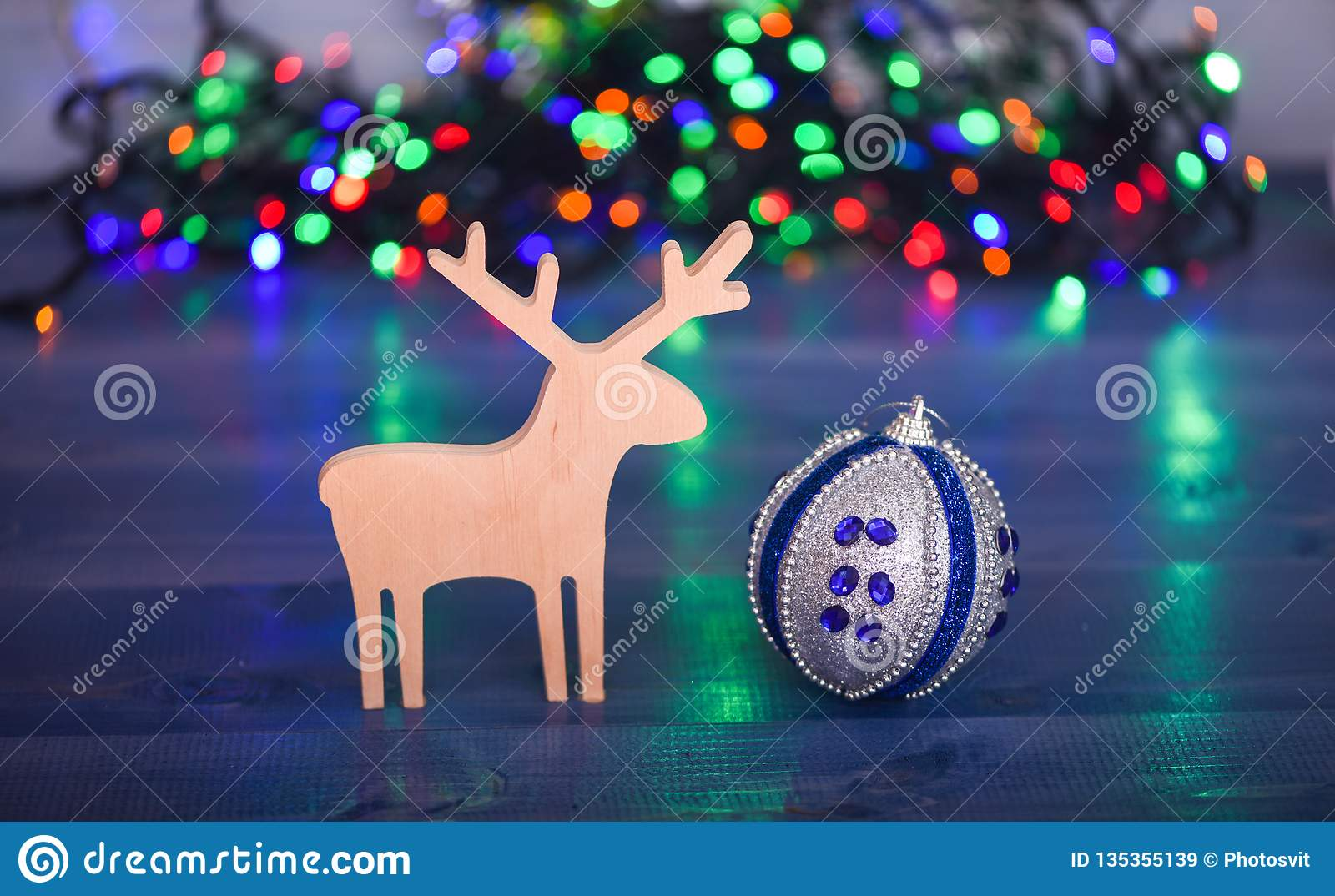 Colorful Christmas Lights Aesthetic.Ball With Ornaments And Wooden Deer Toy On Blurred Colorful
