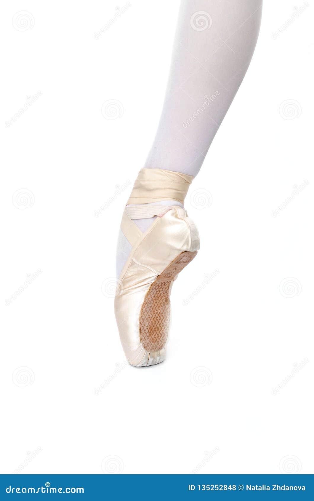 Ballerina`s leg on pointe white background