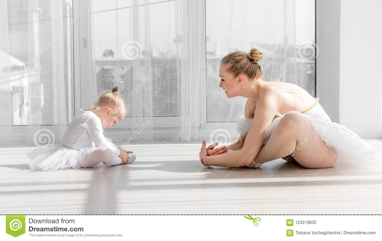 Ballerina with child girl warming up before training
