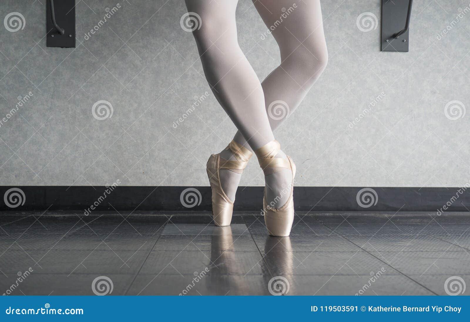 Ballerina dancer in the ballet studio en pointe in releve fourth position
