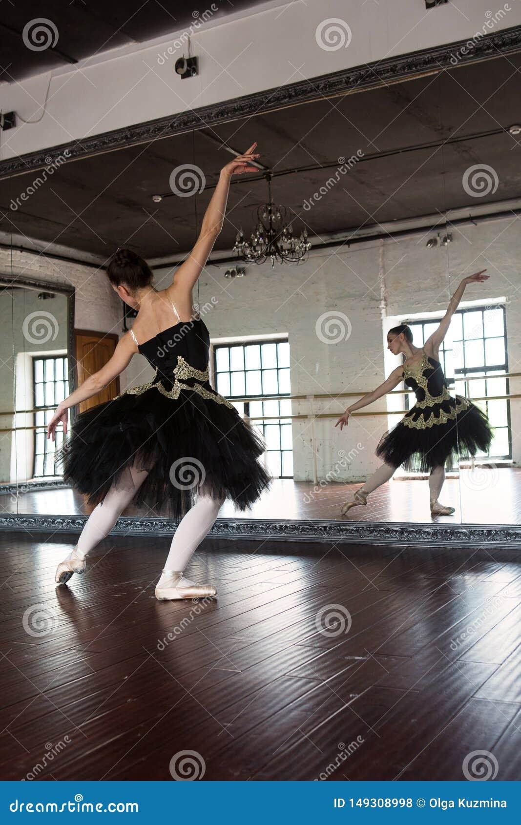 Ballerina di ripetizione nel corridoio Pareti bianche, pavimento di legno scuro, soffitto scuro, bei candelieri, la riflessione d