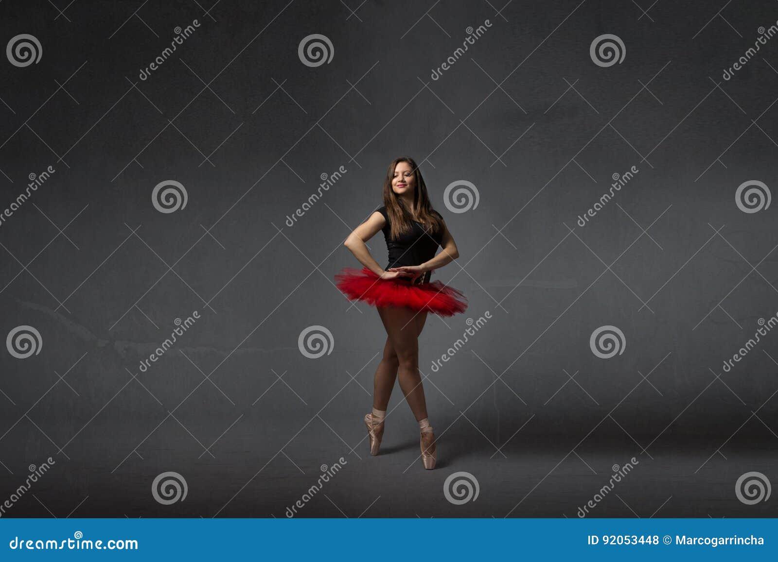 Ballerina die met rode tutu glimlachen