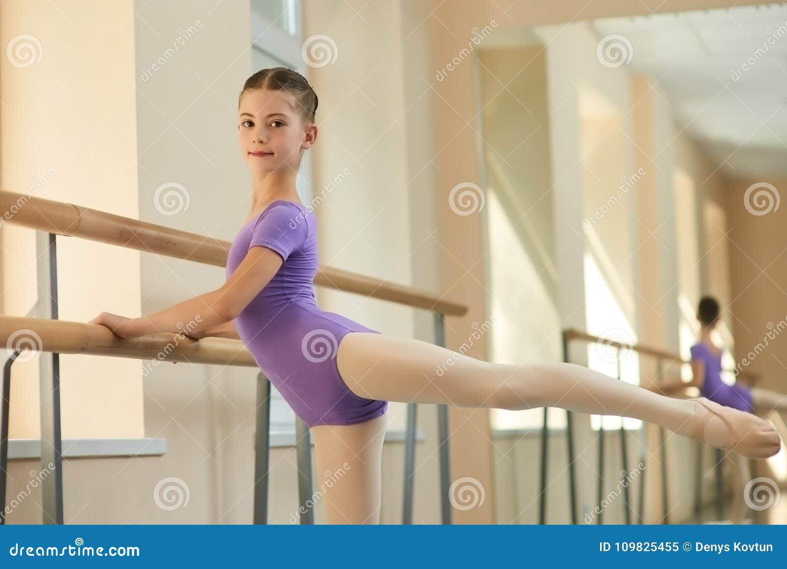 Ballerina die zich uit en camera bekijken uitrekken