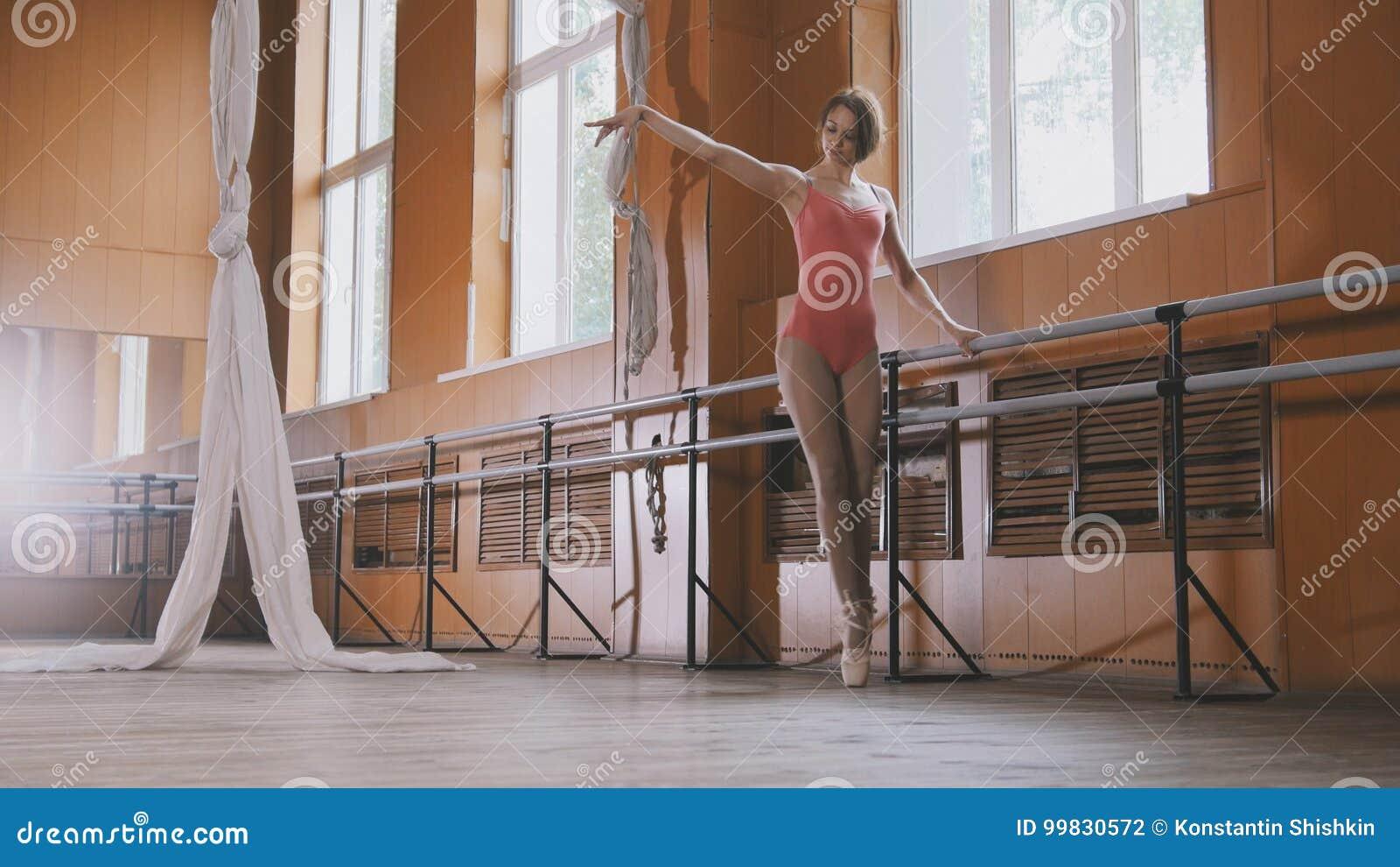 Ballerina graziosa che pratica nello studio, elementi della ragazza del ballo