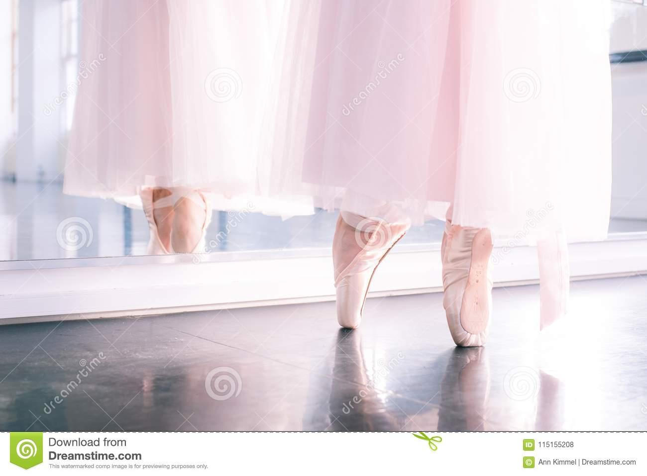 Ballerina`s feet in pointe shoes and pink airy tutu skirt reflecte
