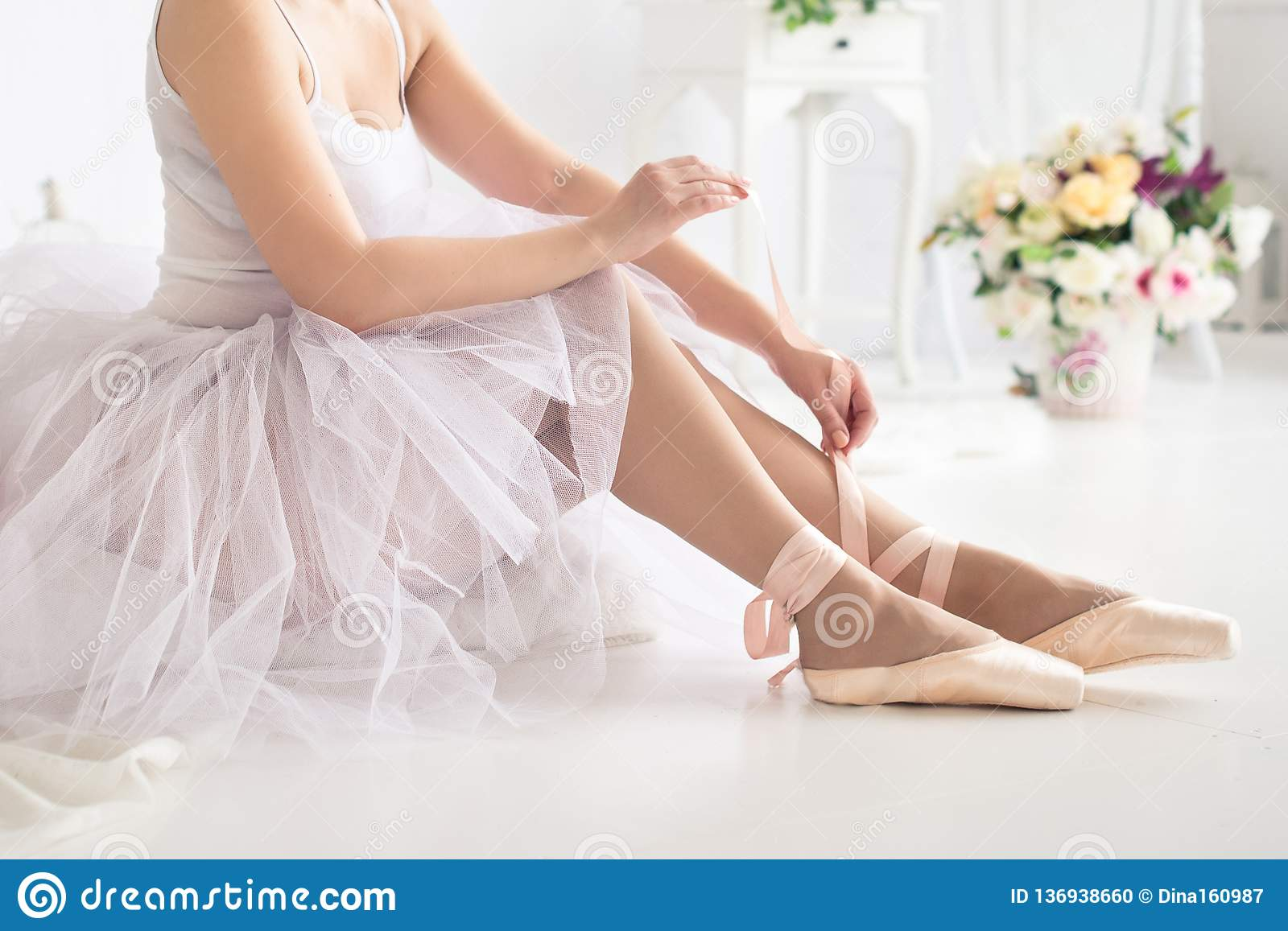 Ballerina tying pointe ballet shoes. Close up