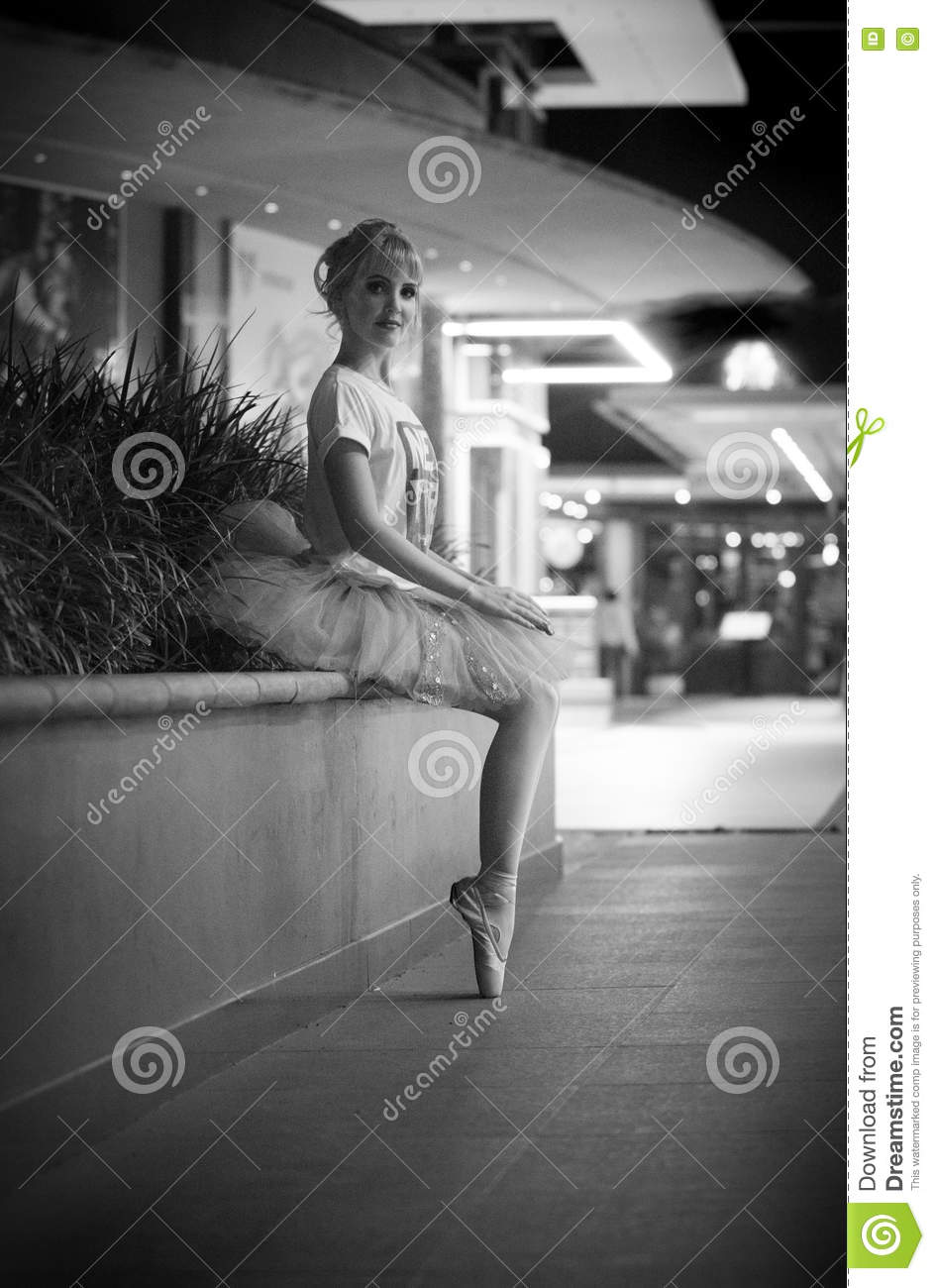 Monochrome black and white portrait of a beautiful blonde ballerina wearing pointe ballet shoes stalkings a tutu and t shirt seated on a bench in an