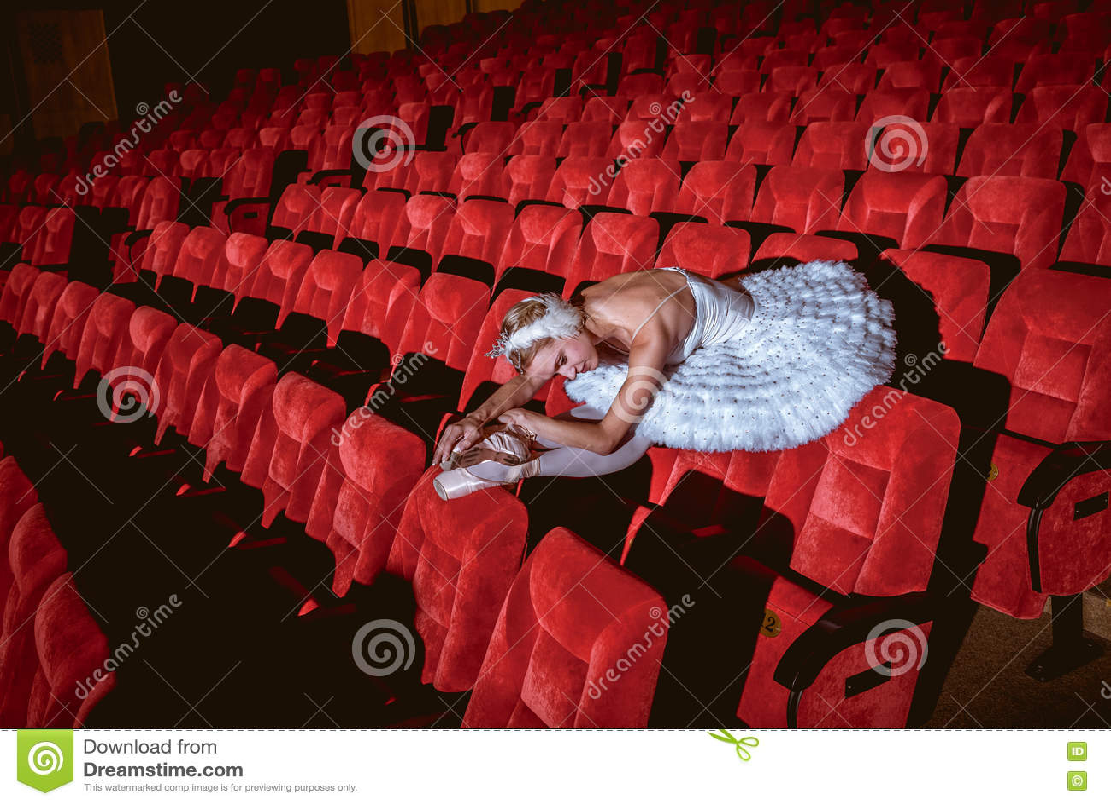 Ballerinazitting in het lege auditoriumtheater
