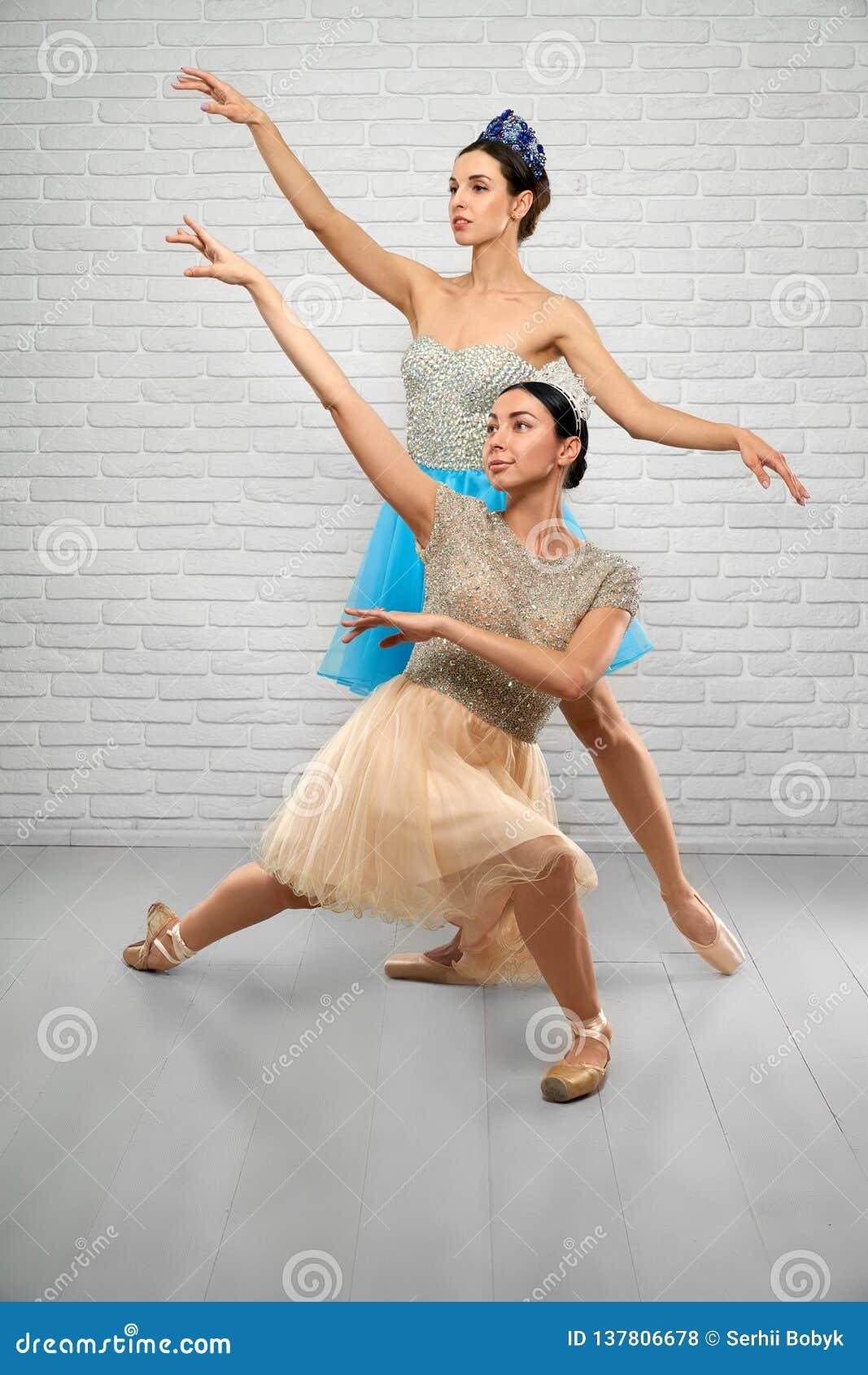Ballerines dans des robes beiges et bleues regardant en haut dans le studio