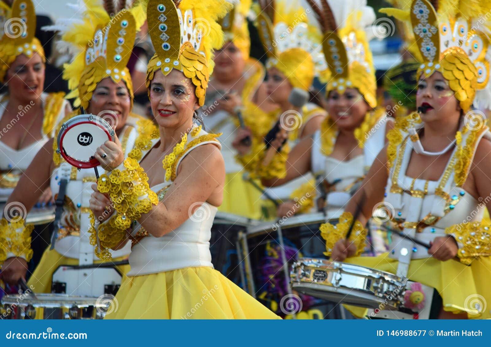 Ballerini e batteristi femminili di carnevale in costumi gialli sgargianti