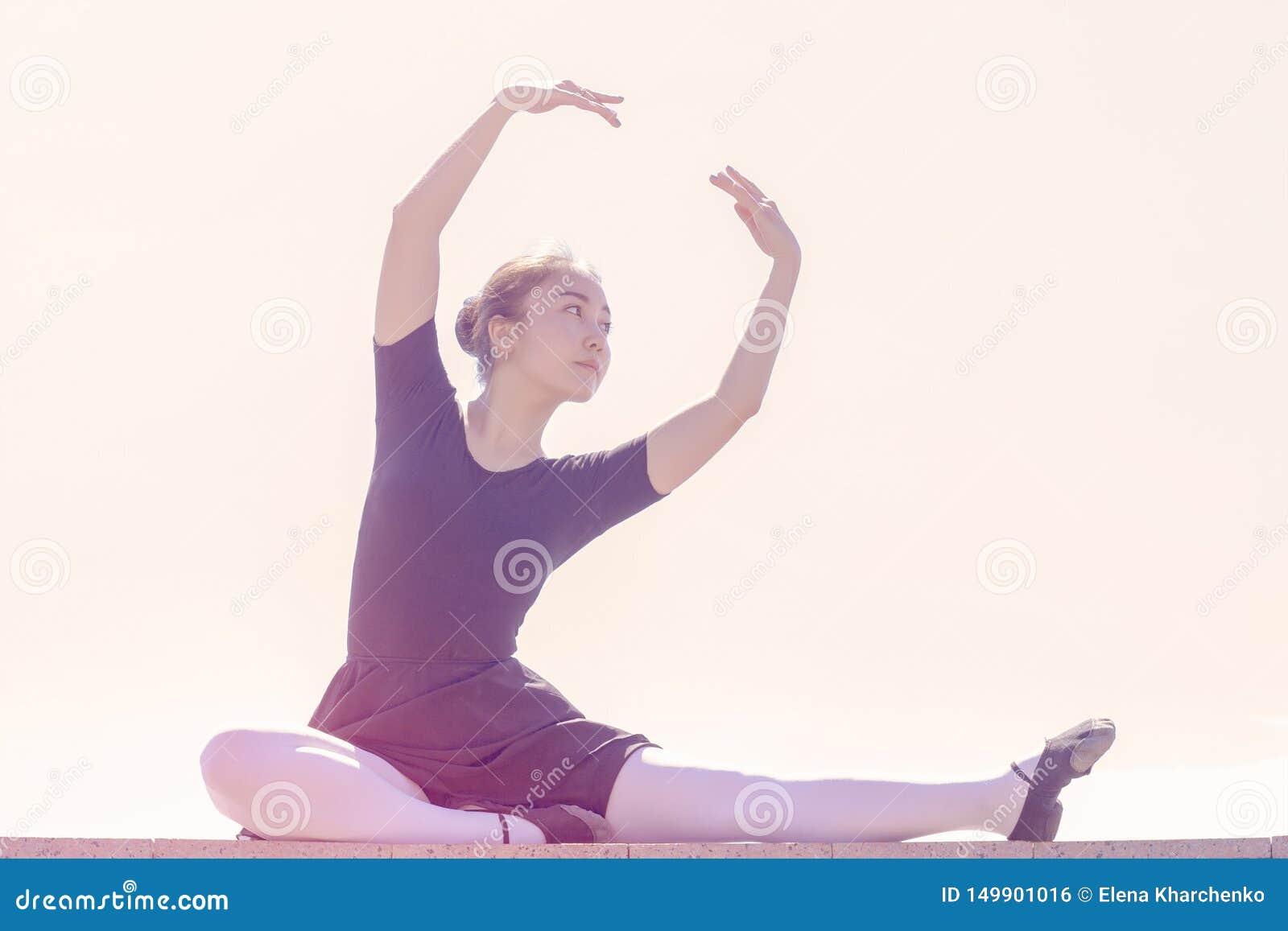 Ballerino della ragazza che fa i movimenti differenti del ballo in costume da bagno per le scarpe di balletto e ballare