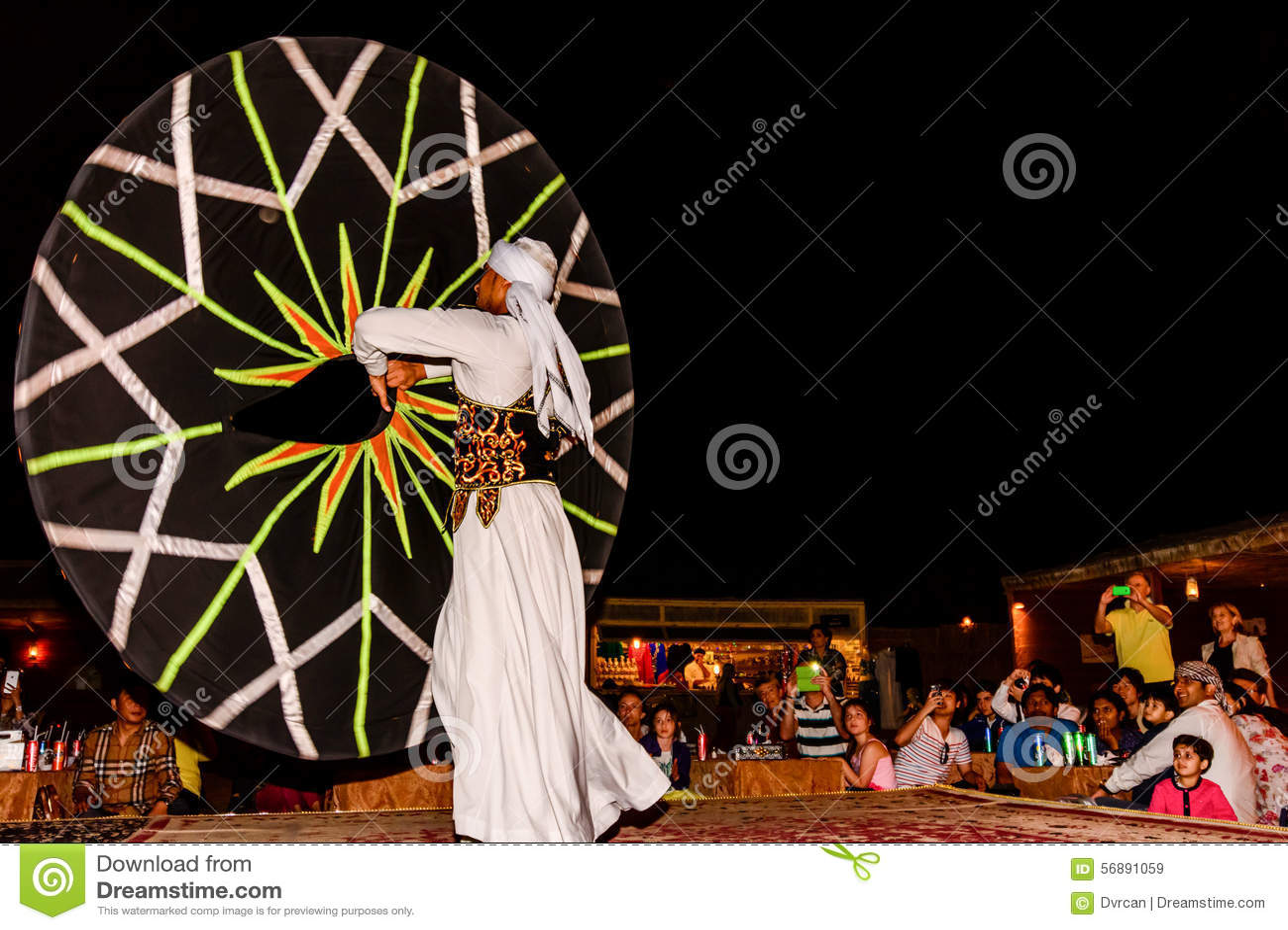 Ballerino maschio arabo che esegue davanti ad una folla nel deser arabo