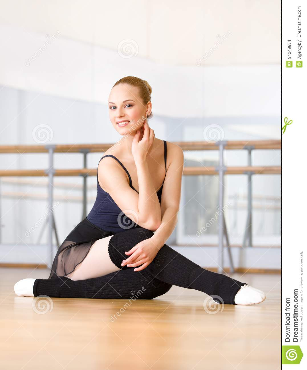 Ballet dancer works out sitting on the wooden floor stock for Dance where you sit on the floor