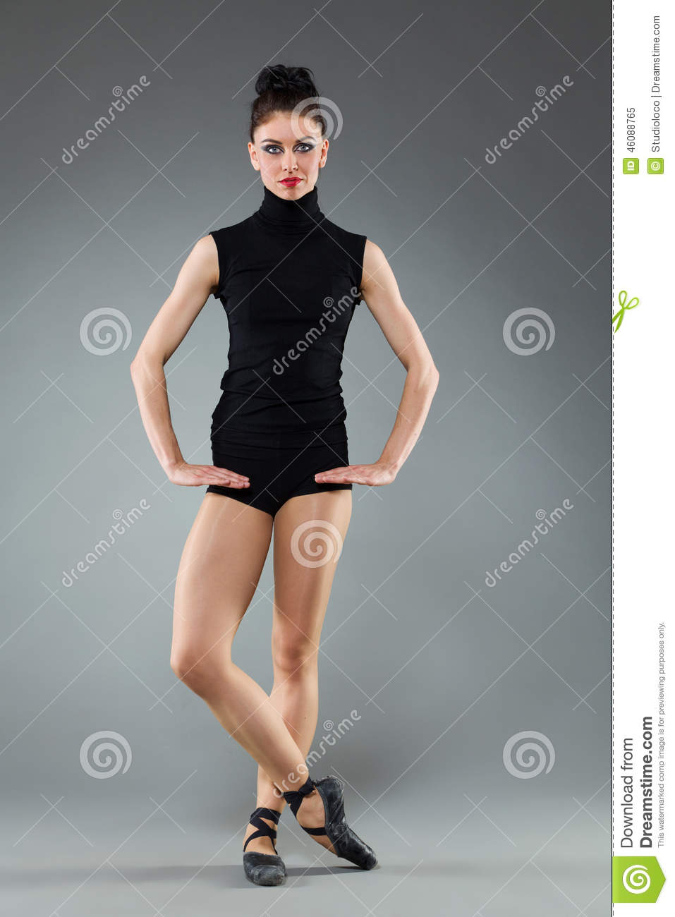 Female ballet dancer is posing with legs crossed at ankle. Full length ...