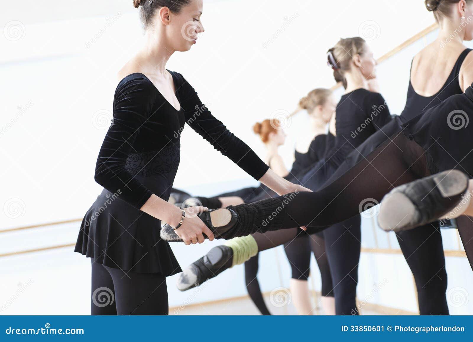 Ballet Teacher Adjusting Foot Positions Of Ballerinas