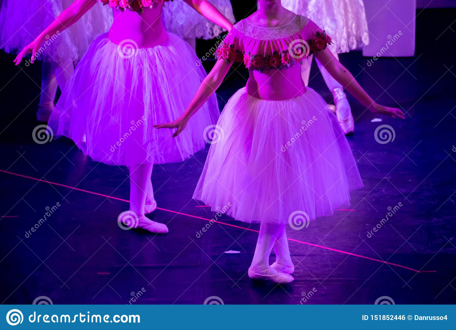 Balletdansers die onder Purper Licht met Klassieke Kleding een ballet op Onduidelijk beeldachtergrond uitvoeren
