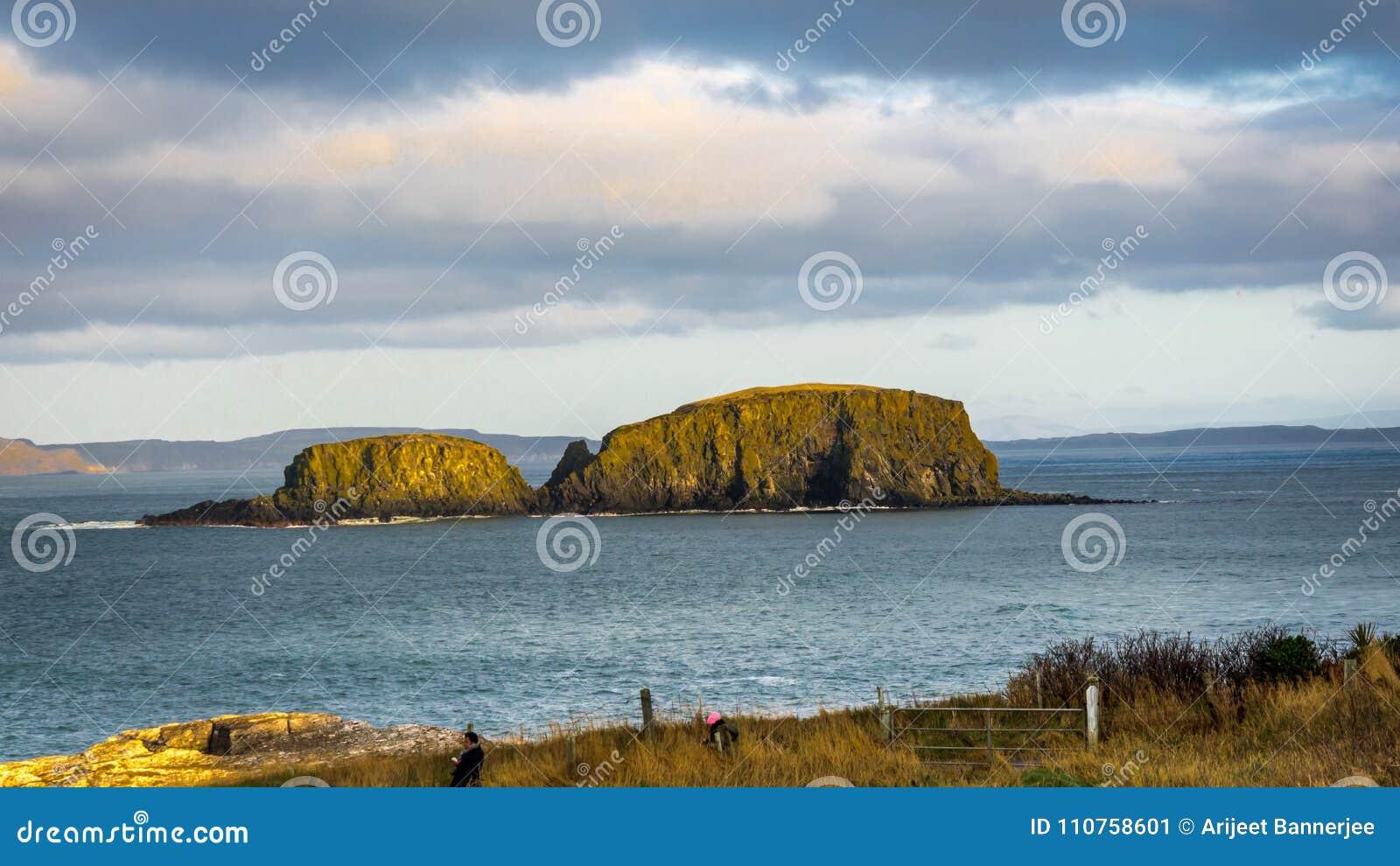 Ballintoy, Republiek Ierland, het UK - 28 December, 2016: Een paar toerist die het schapeneiland fotograferen dichtbij reuzeverho