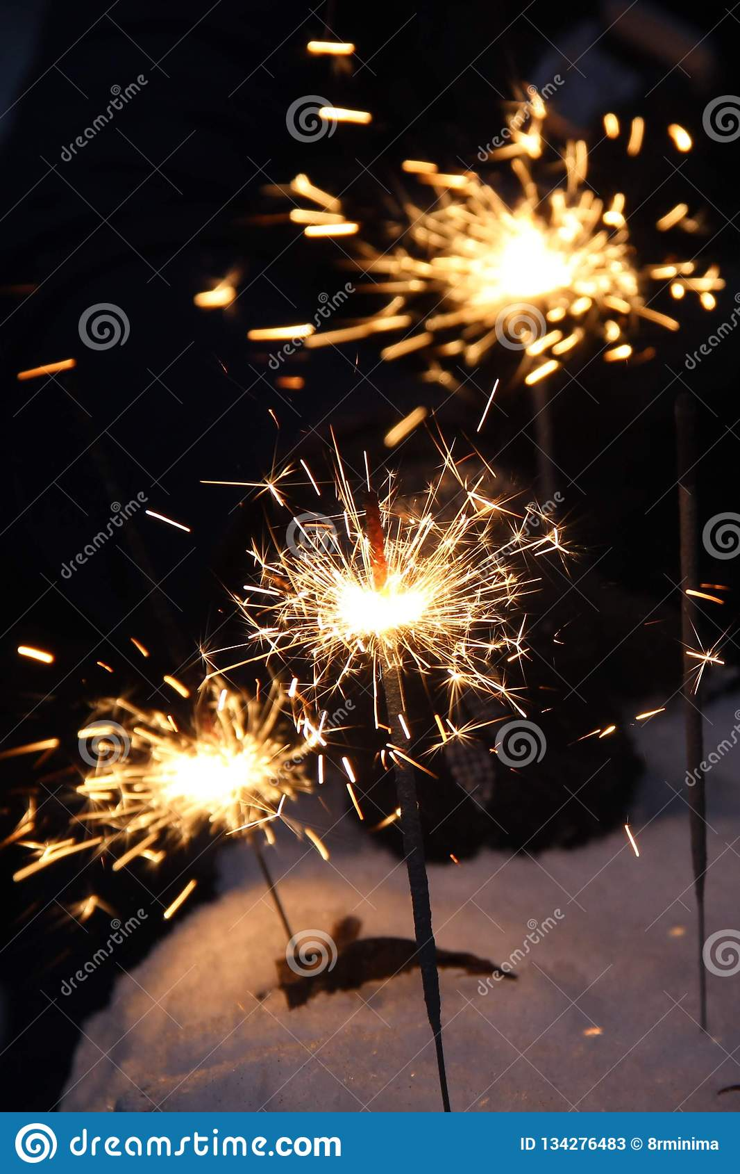 Ballo luminoso delle luci di Bengala nelle ombre di notte su fondo nero un flash luminoso delle stelle filante