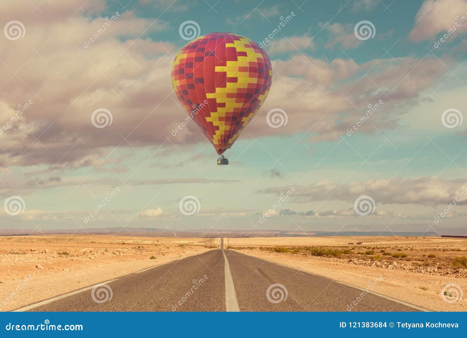 Ballong för varm luft över öken och vägen