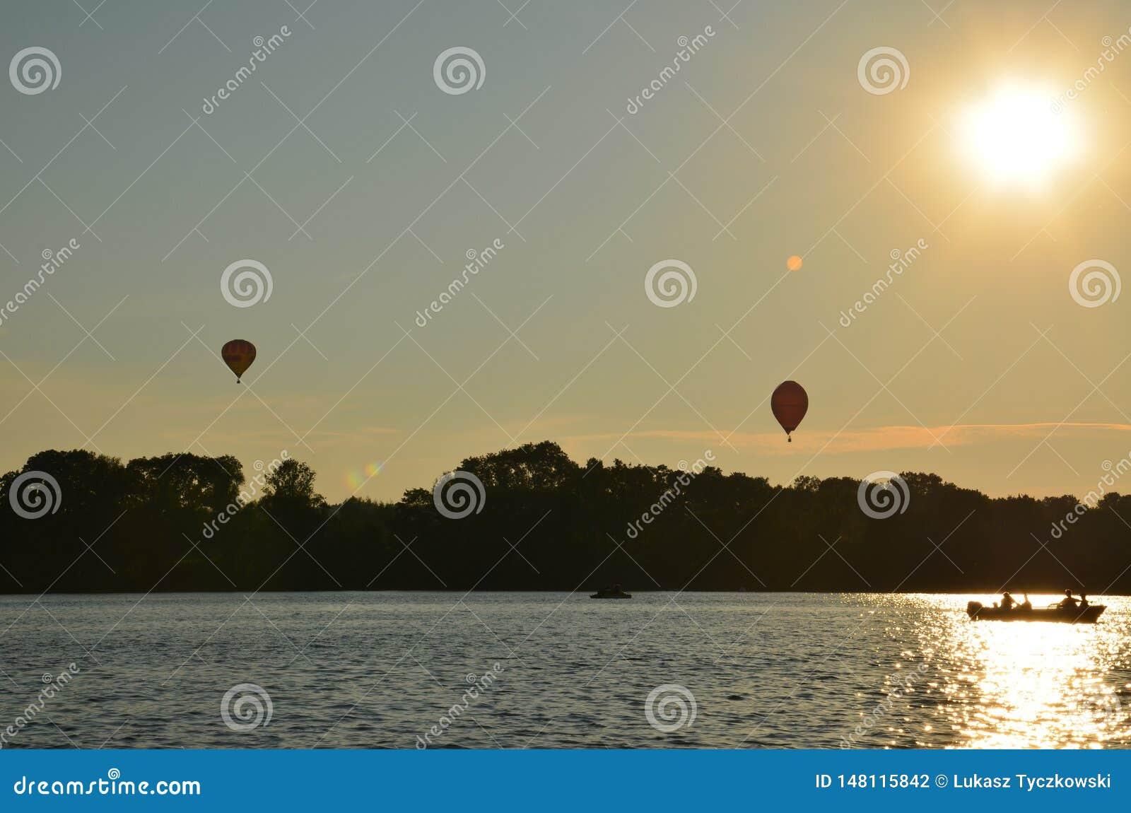 Ballonger f?r varm luft ?ver en sj? i den Polen sikten under solnedg?ng
