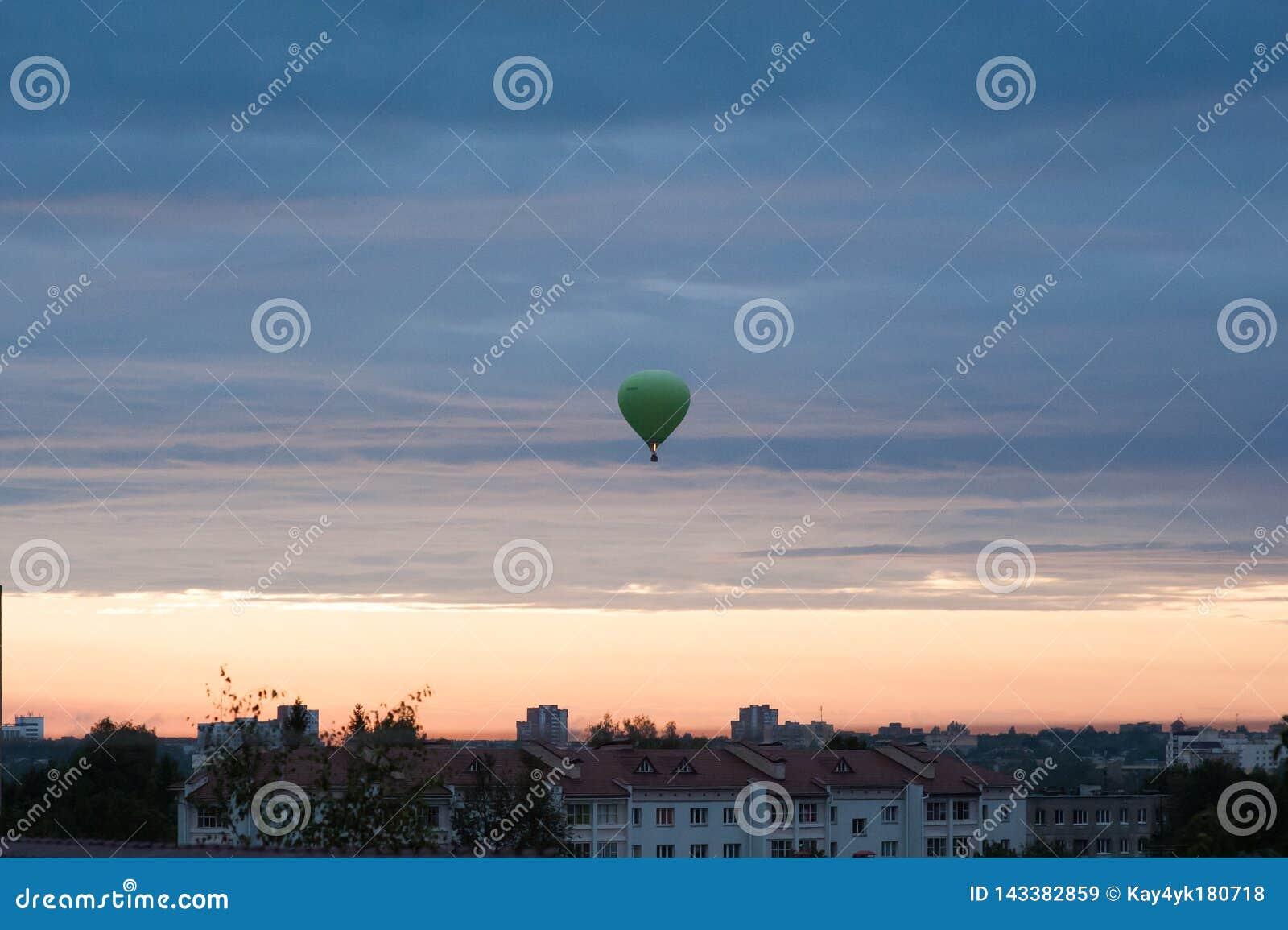 Ballonger flyger upp i himmel med passagerare ?ver gr?nt f?lt E r