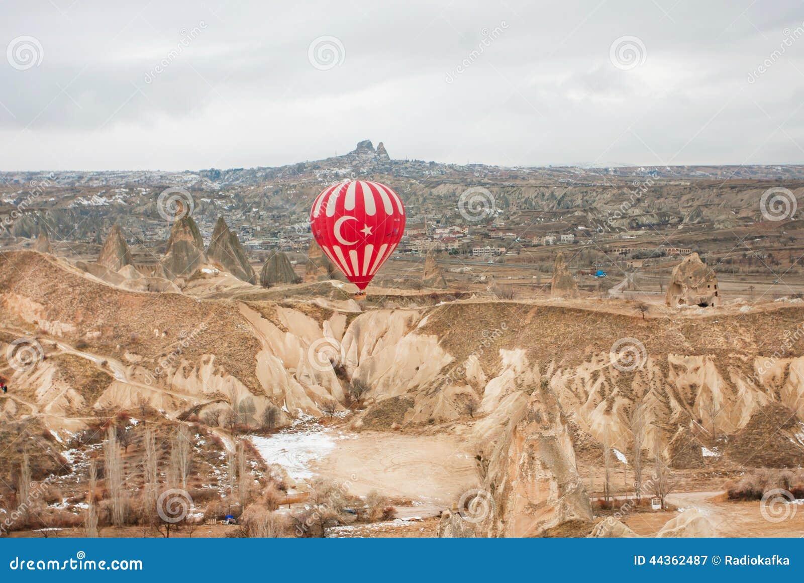 Balloon sopra paesaggio roccioso della valle di Cappadocia a tempo nuvoloso
