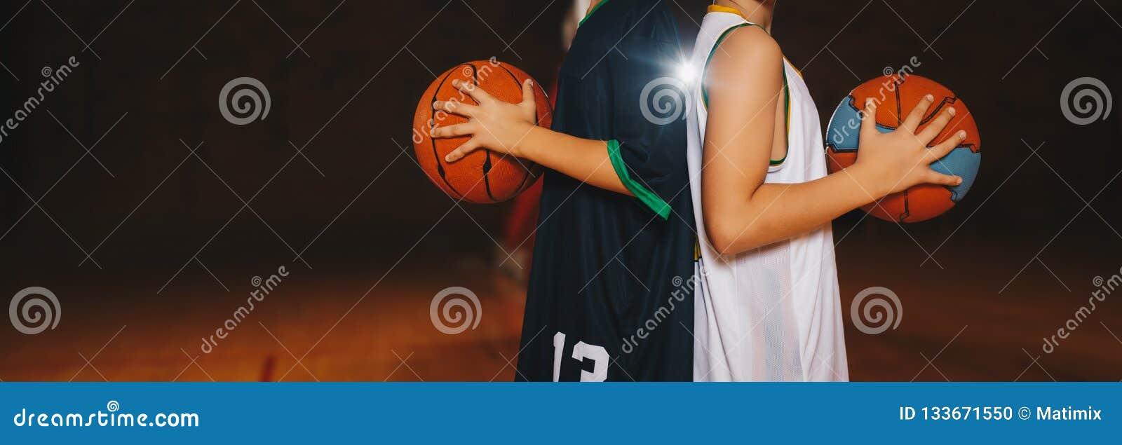 Baloncesto Team Players Holding Basketballs de dos muchachos en la corte de madera Entrenamiento del baloncesto para los niños