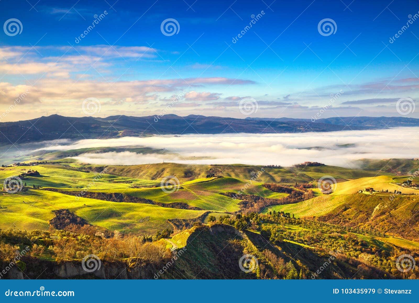 Balze de panorama brumeux de matin de Volterra, de terres cultivables et de fi vert
