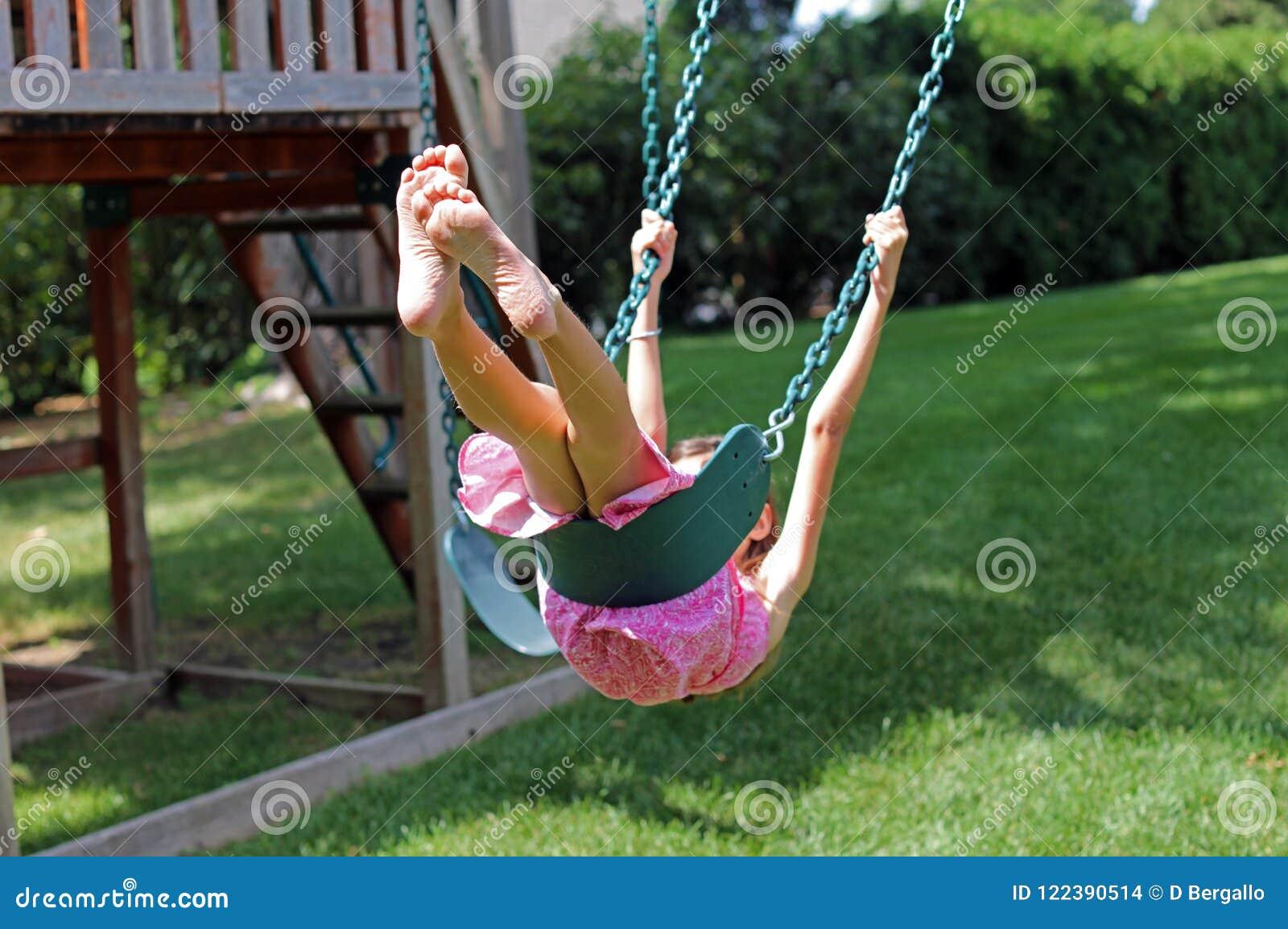 Bambina adorabile alle oscillazioni nel parco con il vestito rosa durante l estate nel Michigan