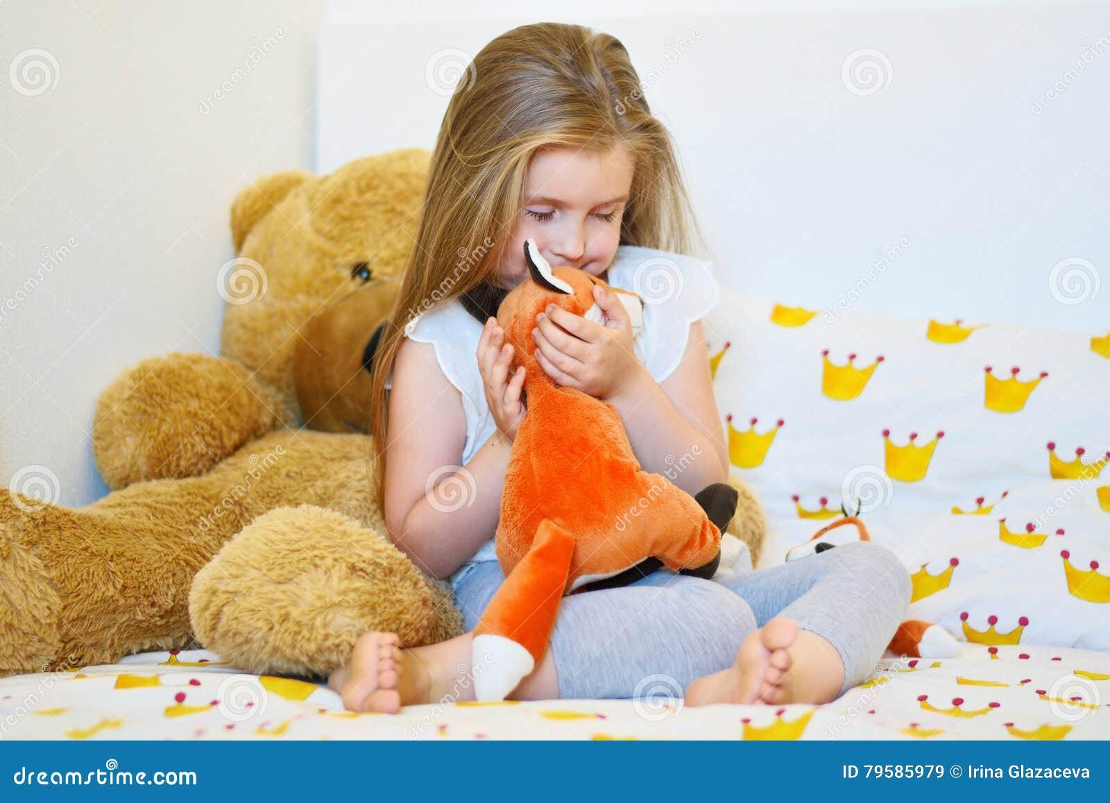 Bambina adorabile che abbraccia il giocattolo della peluche della ...