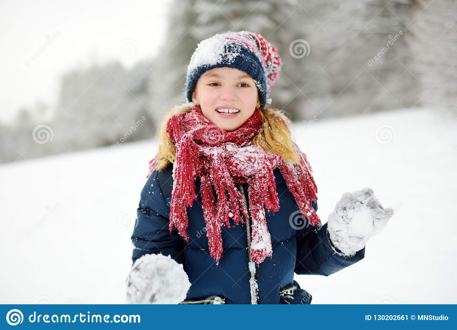 Bambina adorabile divertendosi nel bello parco di inverno Bambino sveglio che gioca in una neve