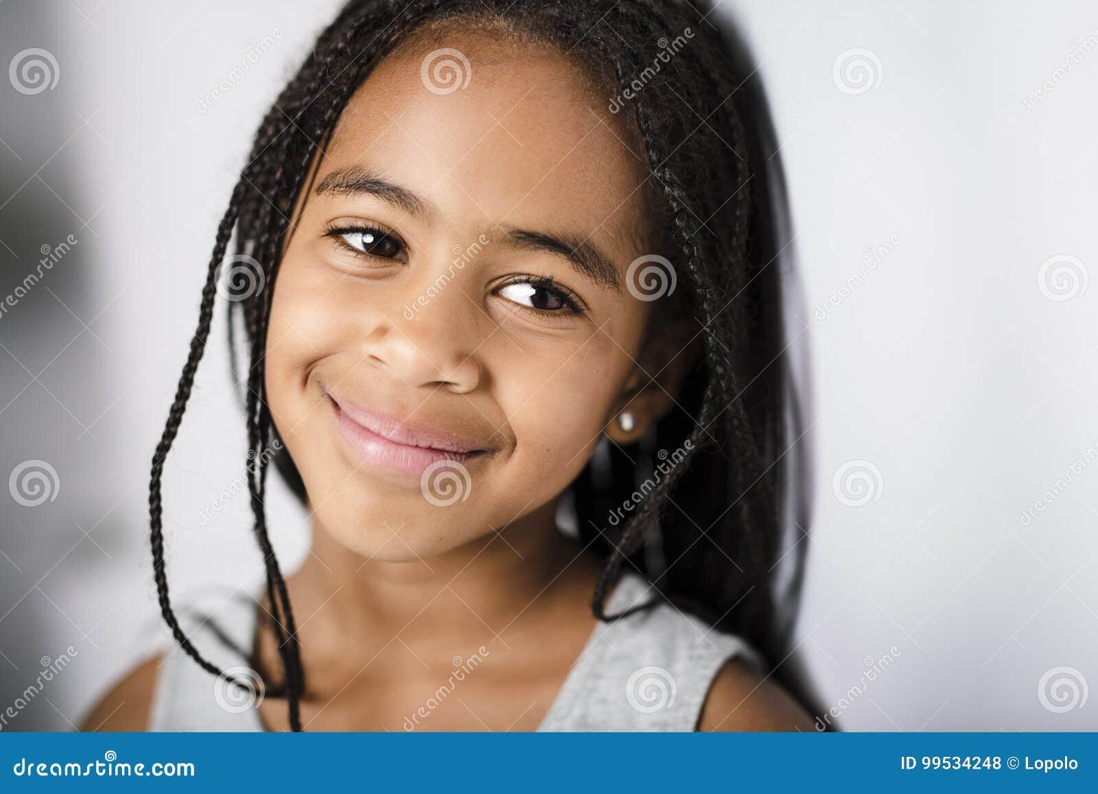 Bambina africana adorabile sul fondo di gray dello studio
