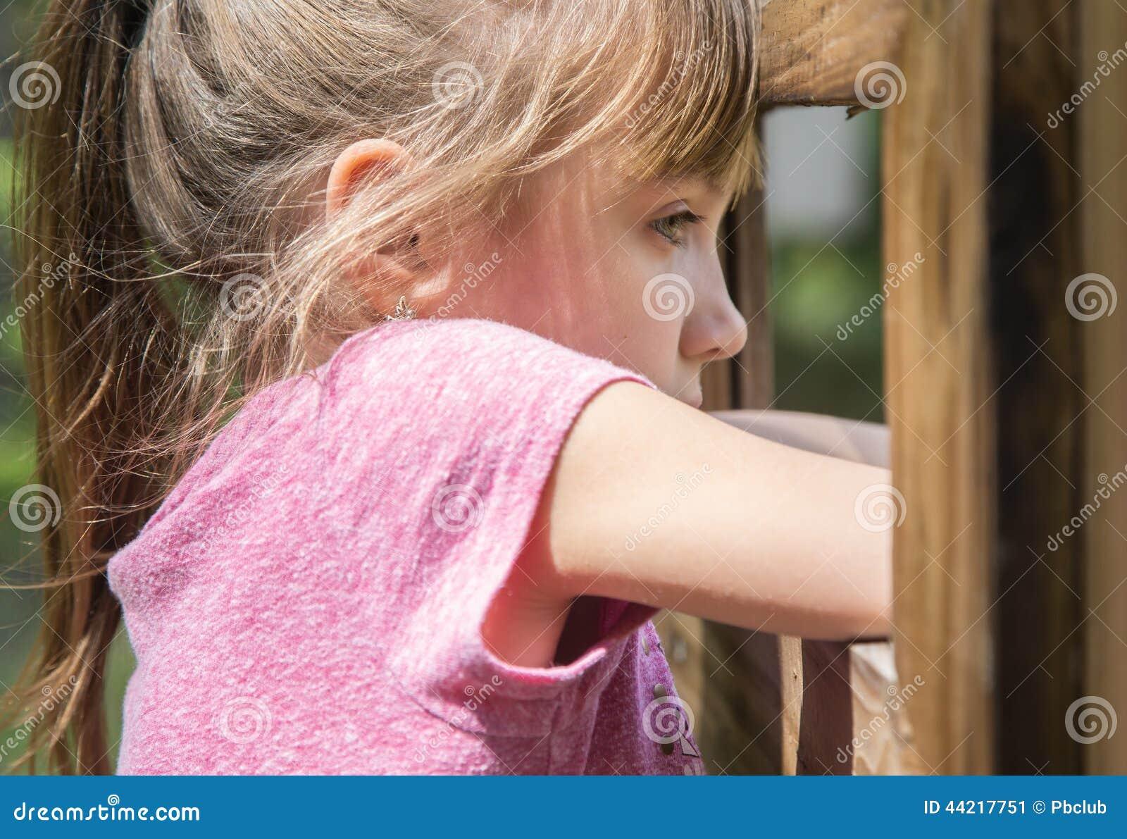 Bambina bionda che guarda fuori