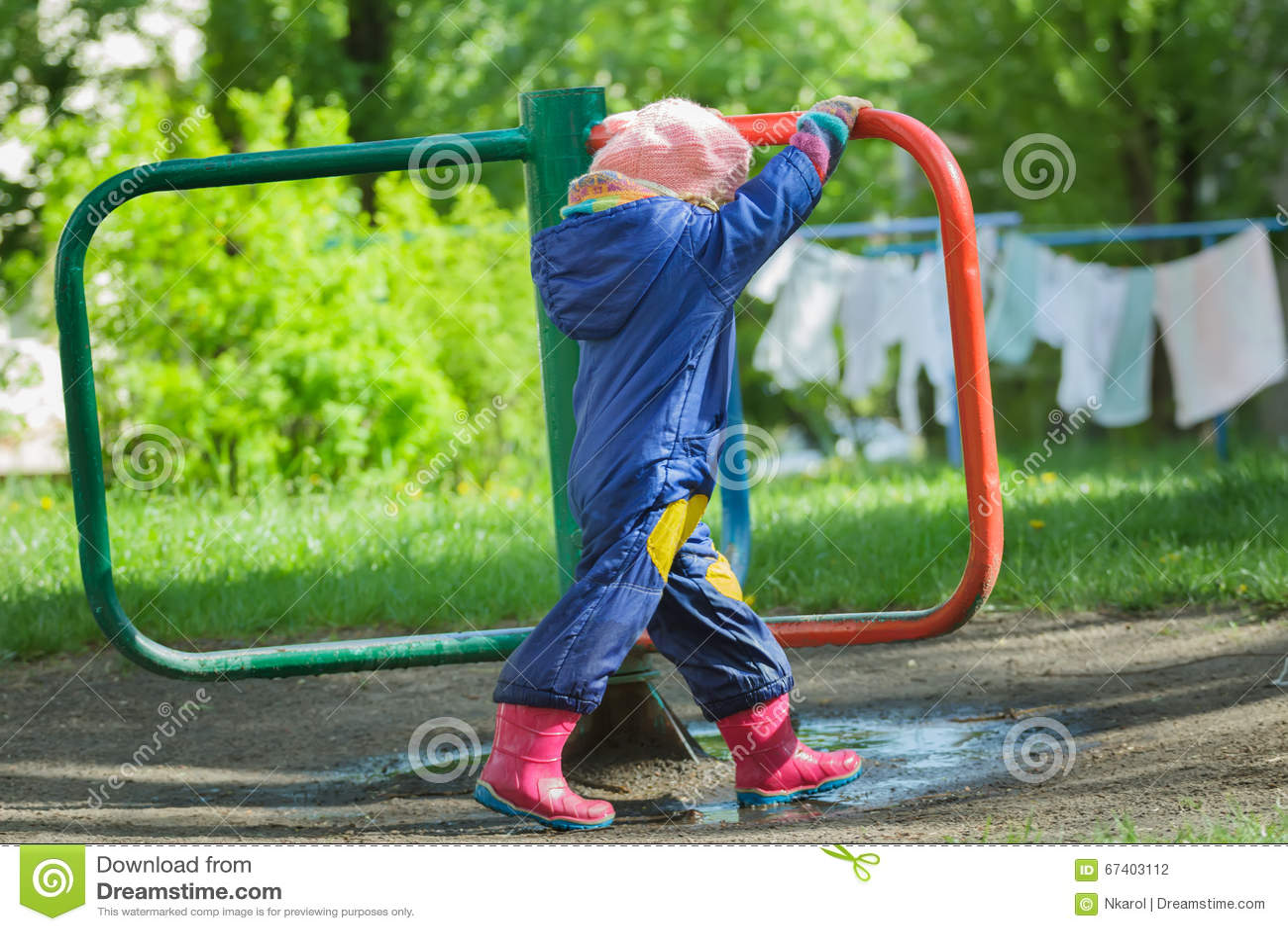 Bambina in carosello girante della rotonda dell annata del boilersuit blu manualmente alle tele di secchezza ed al fondo dell erb