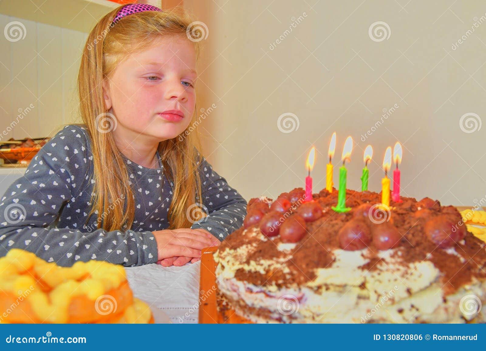 Bambina che considera la sua torta di compleanno Piccola ragazza che celebra i suo sei compleanni Torta di compleanno e bambina