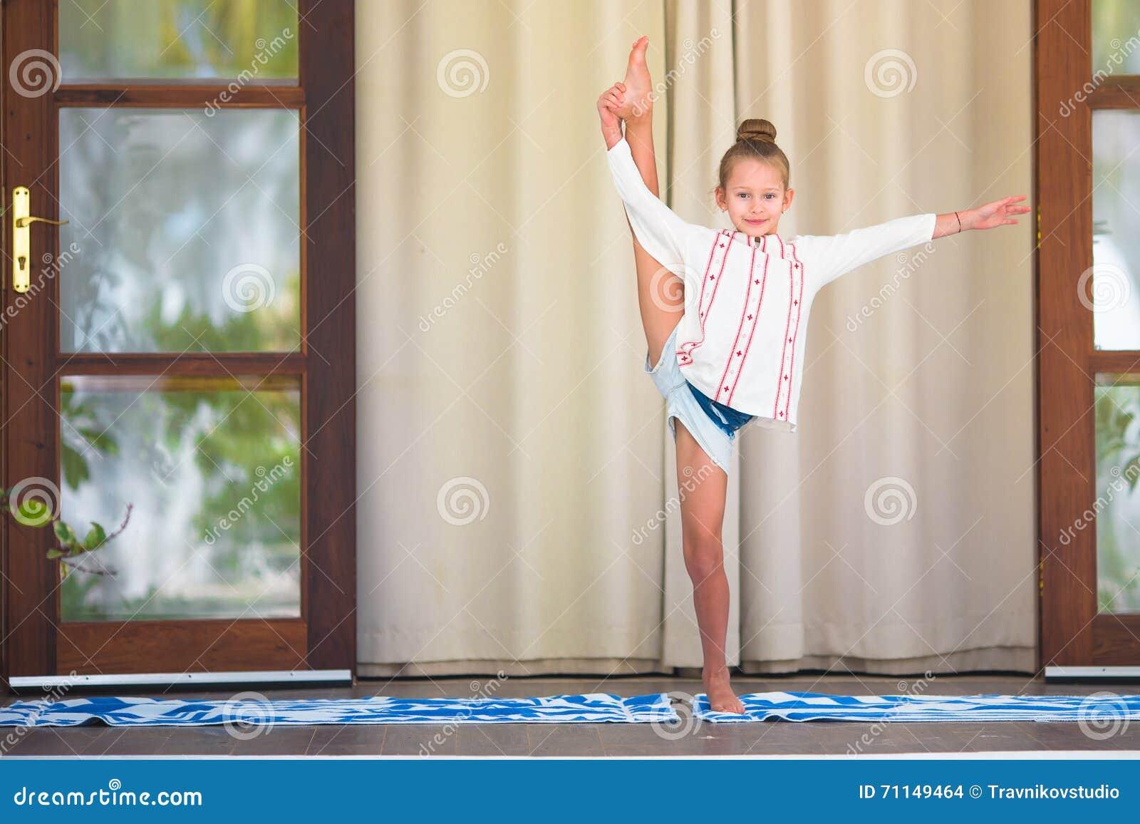 Bambina Che Fa Ginnastica Su Una Stuoia Verde Per Yoga