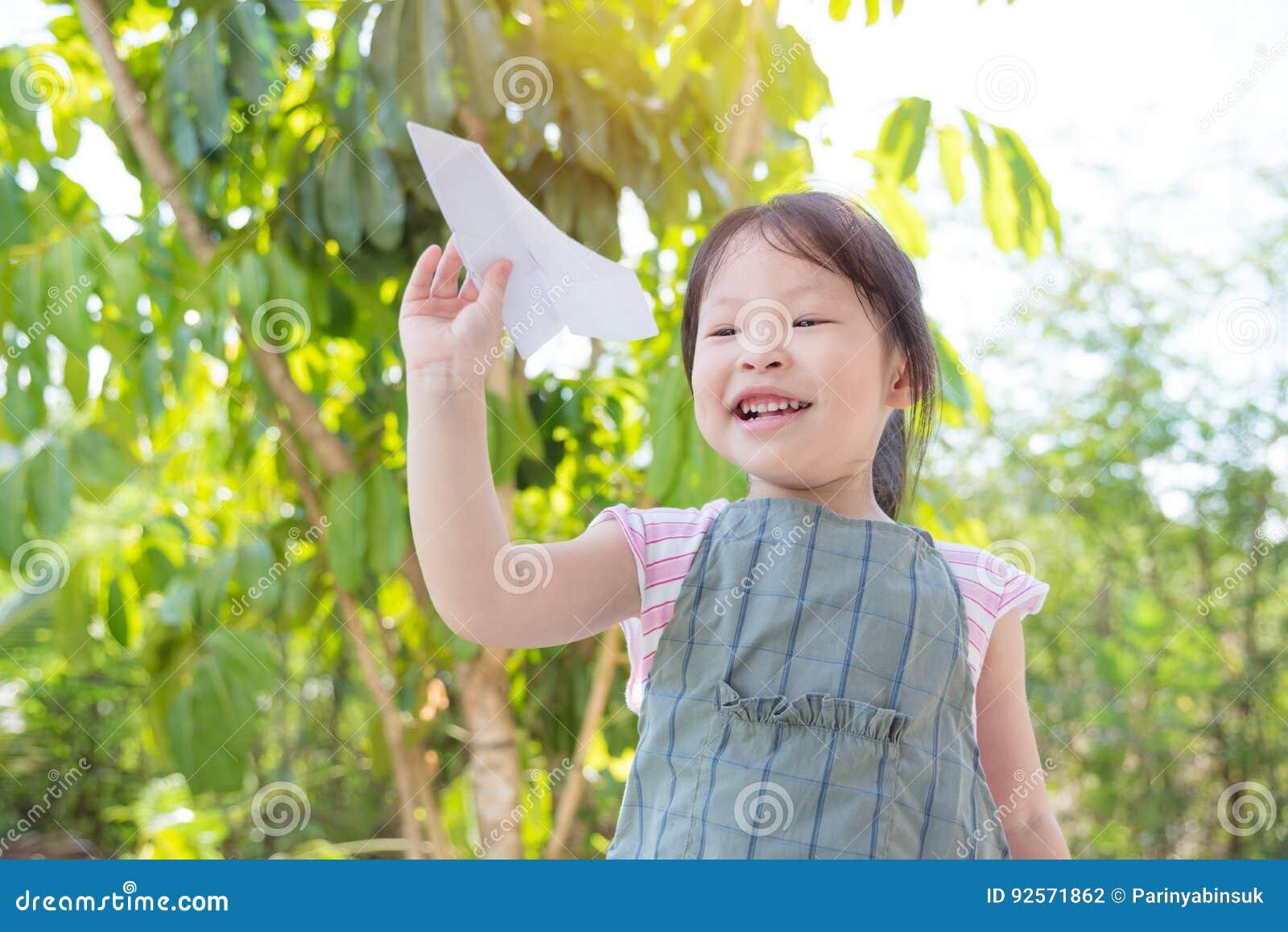 Bambina che gioca aeroplano di carta