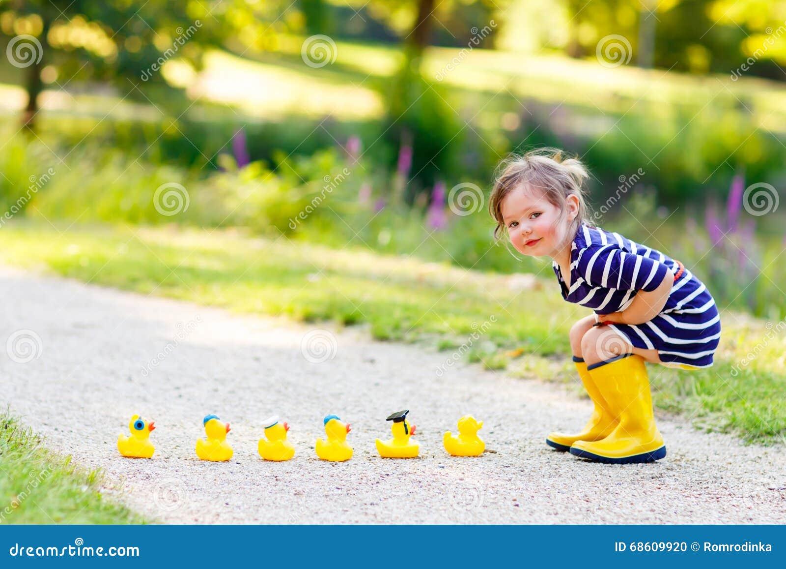 Bambina In Stivali Di Pioggia Che Giocano Con Le Anatre Di