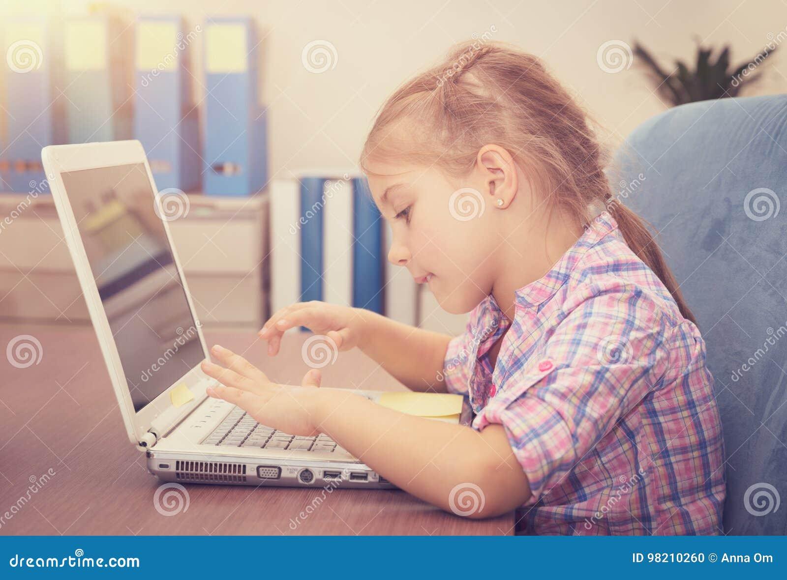 Bambina che lavora al computer portatile