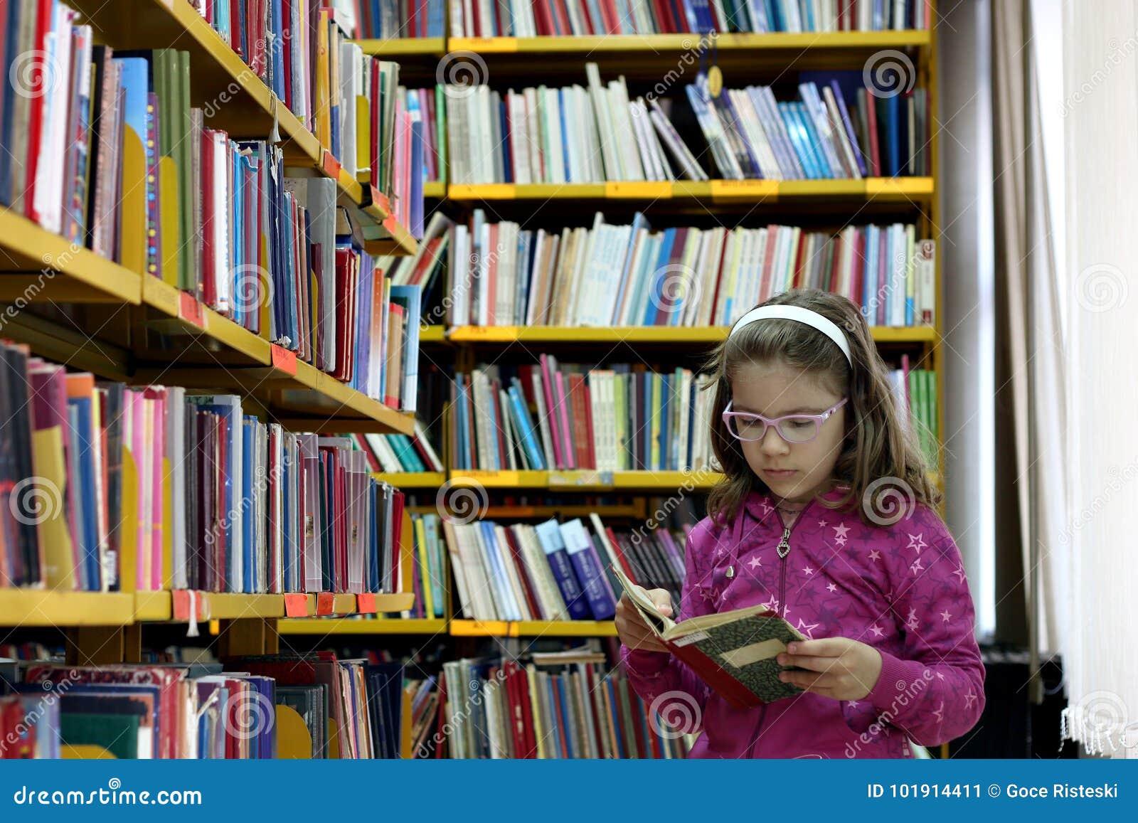 Bambina che legge un libro nella biblioteca
