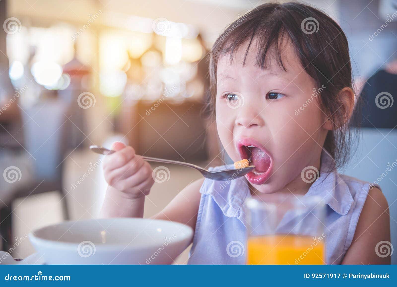 Bambina che mangia cereale per la prima colazione