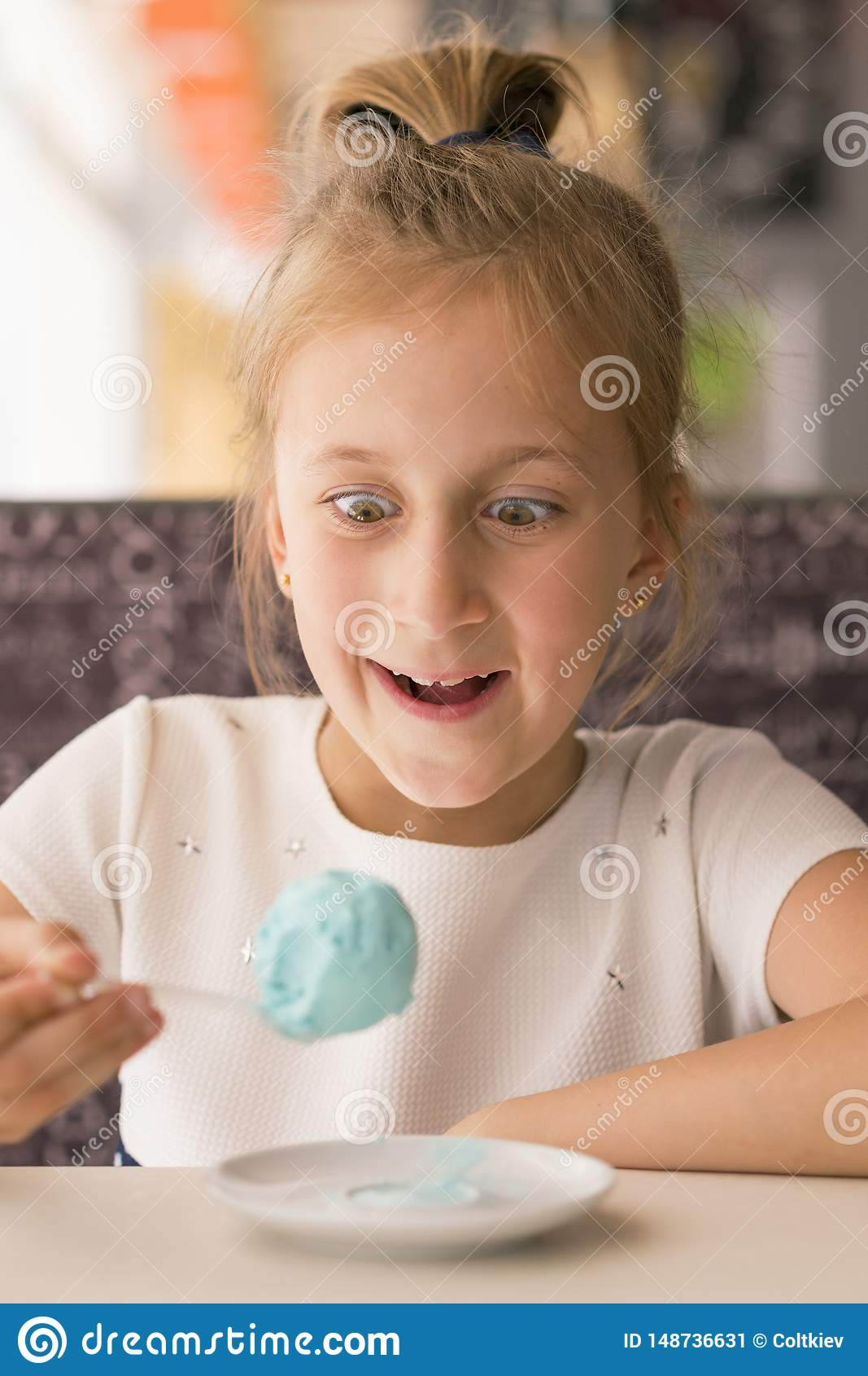 Bambina che mangia il gelato blu in un caff? Ragazza contentissima con il gelato Bambina adorabile che mangia il gelato all estat